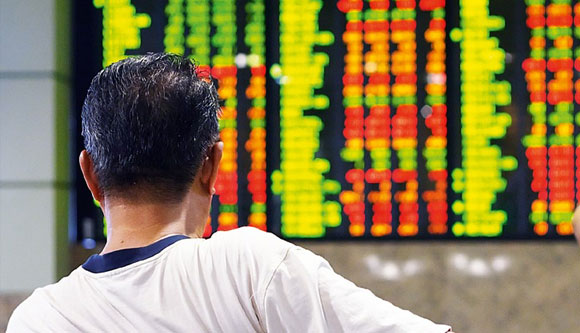 Photo of Filipino man looking at stock monitor